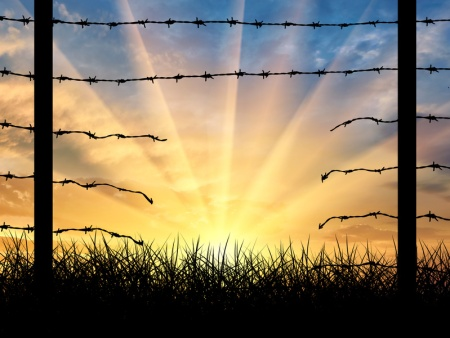 Silhouette of a broken border fence with barbed wire